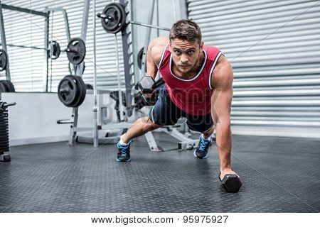 Portrait of muscular man using dumbbells in crossfit gym
