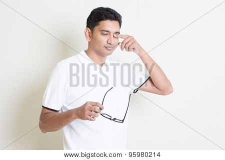 Portrait of Indian guy take off eyeglasses and rubbing his tired eyes. Asian man standing on plain background with shadow and copy space. Handsome male model.