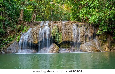 Jangle landscape with flowing turquoise water of third step Erawan cascade waterfall at deep tropical rain forest. Erawan Falls National Park at  Kanchanaburi, Thailand