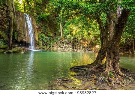 Jangle landscape with flowing turquoise water of second step Erawan cascade waterfall at deep tropical rain forest. Erawan Falls National Park at Kanchanaburi, Thailand