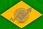 Brazilian Real coins arranged like a growth arrow in front of a one real coin on a brazilian flag background poster