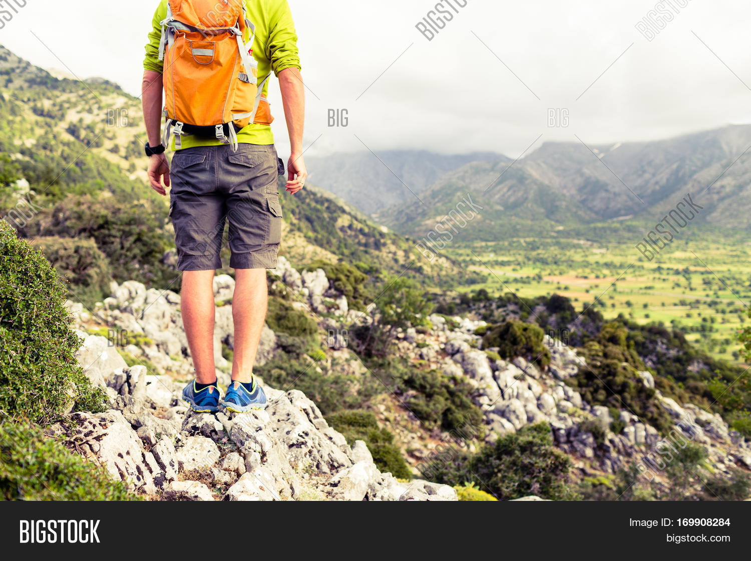 860924da96ac6b Hiking man looking at beautiful mountains inspirational landscape. Hiker  trekking with backpack on rocky trail