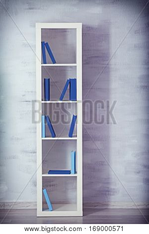 White wooden shelving with books on gray wall background