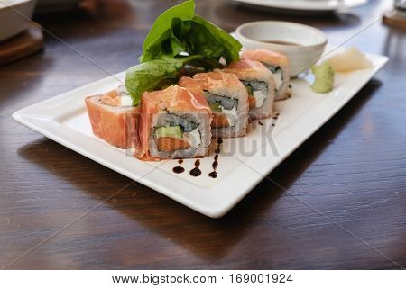 Closeup fusion salmon sushi rolls with sauce on white plate; healthy and fusion japanese food style concept