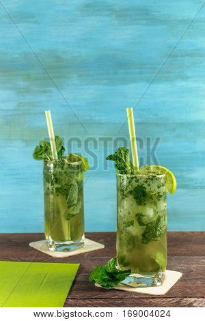 A photo of mojito cocktails with mint leaves and wedges of lime on a vibrant teal wooden background with copy space. Selective focus