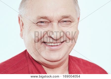 Close up portrait of laughing aged man wearing red shirt against white background - wellbeing concept