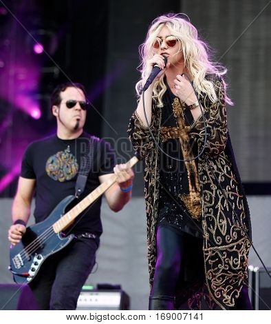 LAS VEGAS-SEP 20: Singer Taylor Momsen (R) and Mark Damon of The Pretty Reckless perform at iHeartRadio Music Festival Village Show at MGM Resorts Village on September 20, 2014 in Las Vegas, Nevada.