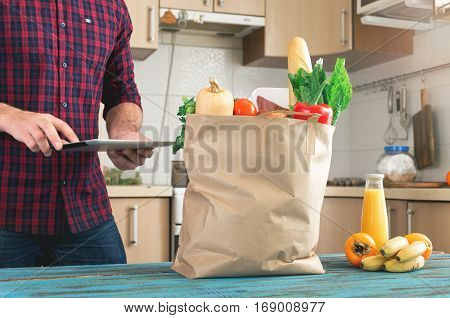 In the home kitchen on wooden table stand full bag of healthy food close up