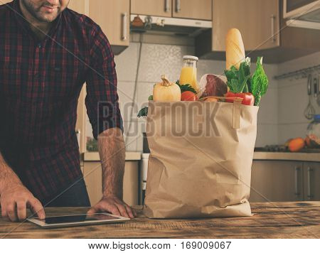 Full paper bag of different vegetables and fruit on a wooden table close up. In the background a man is shopping via the Internet using the tablet