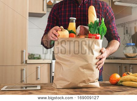 Man examines food from a paper bag on a wooden table in the home kitchen close up
