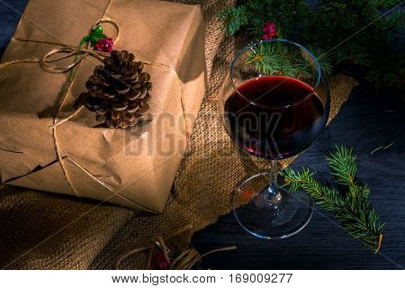 Wrapped gift. On top is a pine cone. A glass of red wine nearby. The dark background