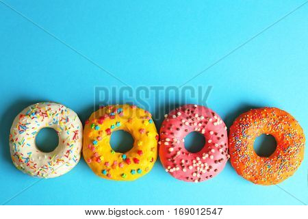 Glazed donuts on color background