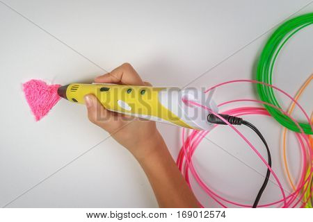 Kid hand holding yellow 3D printing pen with filaments and makes heart on white background. Top view. Copy space for text. Selective focus