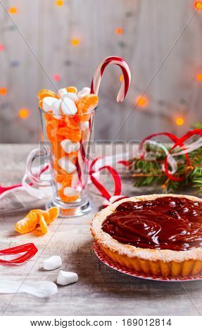 Mandarine tart pouring chocolate. Glass cup witn mandarine and marshmallows on background. Selective focus
