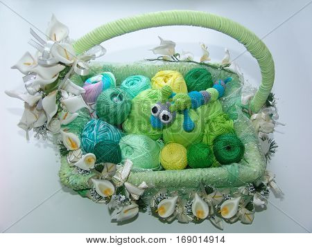 Basket. Greenish yarn. Colored balls of yarn. Valentine. All colors.