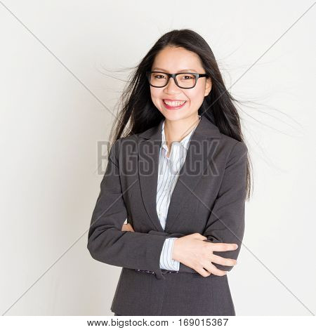 Portrait of young Asian businesswoman in formalwear smiling and looking at camera, standing on plain background.