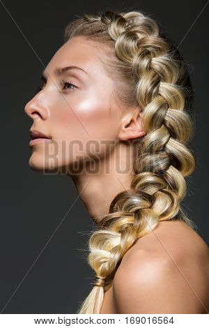 Beautiful young woman with blond hair in french braid and natural make up on black background. Copy space.