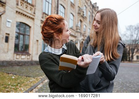 Portrait of a happy two girls reading book together at university campus