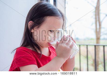 Little asian girl drinking milk from glass