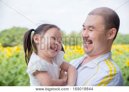 Asian father and his daughter smiling in park