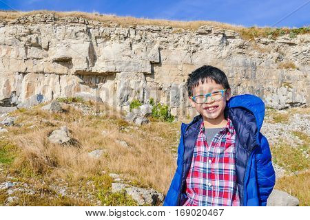 Young asian boy with blue jacket smiling on hill