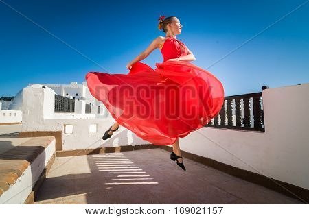 Attractive flamenco dancer wearing traditional red dress with flower in her hair