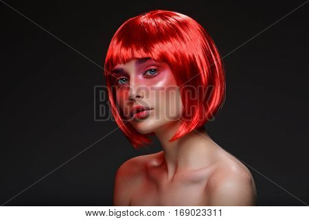 Beautiful young woman with glowing skin, fashion smokey make-up in short red hair wig. Beauty shot on black background. Copy space.