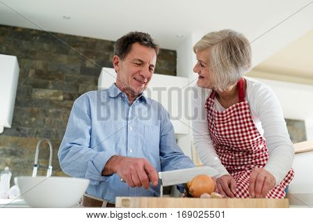 Senior couple in the kitchen cooking together, man cutting onion talking to his wife