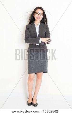 Portrait of young Asian business woman in formalwear smiling, full body standing on plain background.