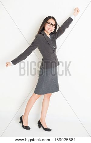 Portrait of happy Asian businesswoman in formalwear arm raised grabbing something and smiling, full body standing on plain background.