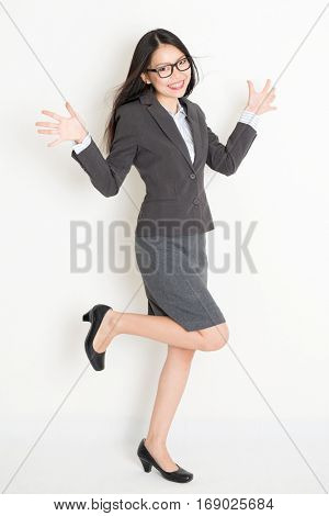 Portrait of happy Asian businesswoman in formalwear smiling, full body standing on plain background.