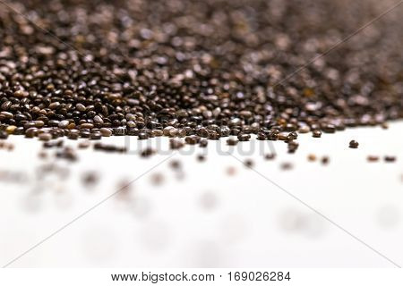 Close up of chia seeds (Salvia hispanica) on a white isolated background. Selective focus. Chia seeds also known as superfoods and used in a wide spectrum of diets.