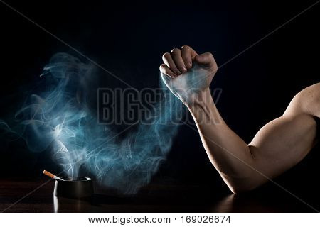 stop smoking concept. Human hand is struggling with a hand of smoke
