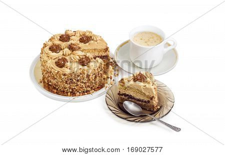 Piece of layered sponge cake decorated with butter cream caramelized condensed milk and nuts with spoon on a glass saucer partly sliced cake and coffee with cream in white cup on a light background