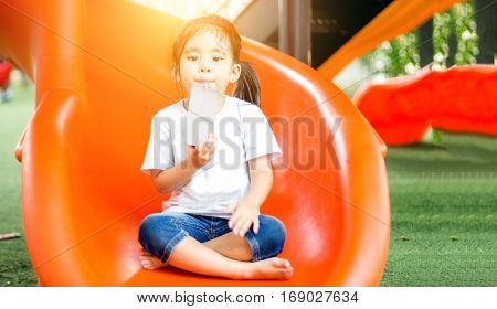 Asian Girl Drink Milk And Play On Playground