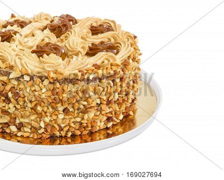 Fragment of a round sponge cake decorated with butter cream and caramelized condensed milk sprinkled with grated nuts on a light background