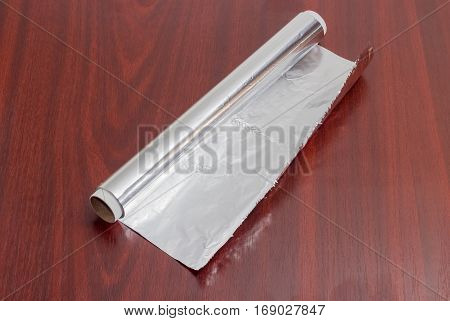 Roll of the aluminum foil for household use on a dark red wooden surface