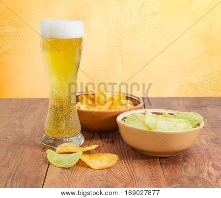 Beer glassware with the lager beer two different kinds of the potato chip flavored paprika and wasabi in ceramic bowls on an old wooden table on a background of an yellow wall
