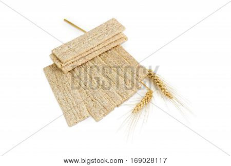 Dietary wheat wholegrain crispbread with adding buckwheat and barley and two wheat spikes on a light background