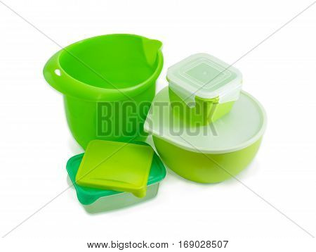 Several different green reusable plastic food storage and cooking containers some with covers for home use on a light background