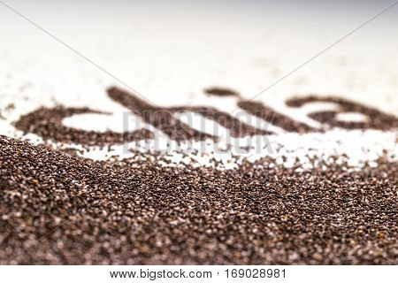 Chia word made from chia seeds (Salvia hispanica) on white background. Chia seeds also known as superfood and used in a variety of healthy diets.