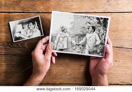 Hand of unrecognizable man looking at various black and white pictures of senior couple in love. Studio shot on wooden background.