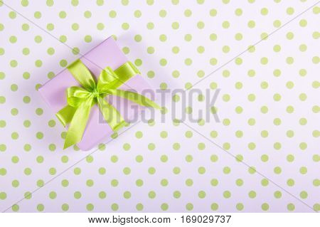 Lilac gift box with satin bow on a polka dot background. Copy space.