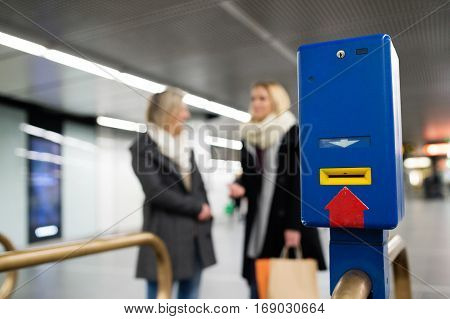 Railway or underground entrance to the station with turnstile. Two unrecognizable women with shopping bags talking.