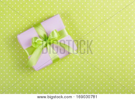 Lilac gift box with a bow on a light green background. Box with surprise on a polka dot background. Copy space.