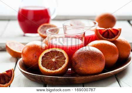 Fresh cold juice with red oranges on white wooden background selective focus