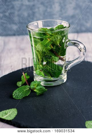 Fresh organic mint tea in glass on wooden background vertical selective focus