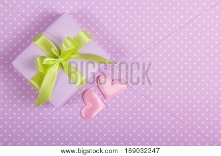 A small box with a bow and valentines on a polka dot background. Valentine's Day. Copy space.