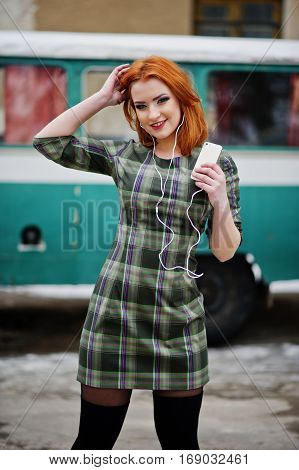 Young Red Haired Girl Lady With Mobile Cell Phone And Headphones, Wearing On Checked Dress Backgroun