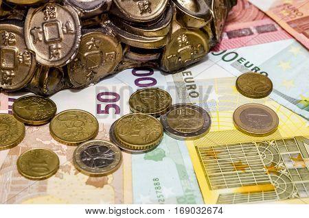 Piggybank coins and euro bills - close up